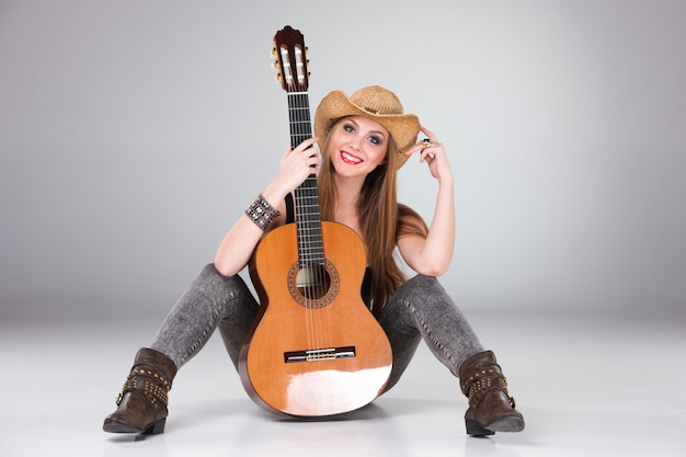The beautiful girl in a cowboy's hat and acoustic guitar. Free Photo