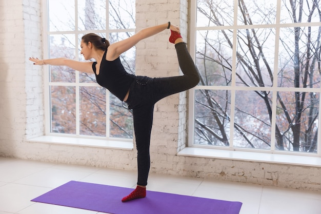 Beautiful girl doing yoga pose to left standing on the floor opposite the window in a bright room. Premium Photo