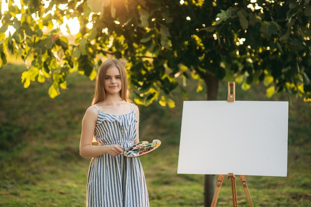 Beautiful girl draws a picture in the park using a palette with paints and a spatula. easel and canvas with a picture. Premium Photo
