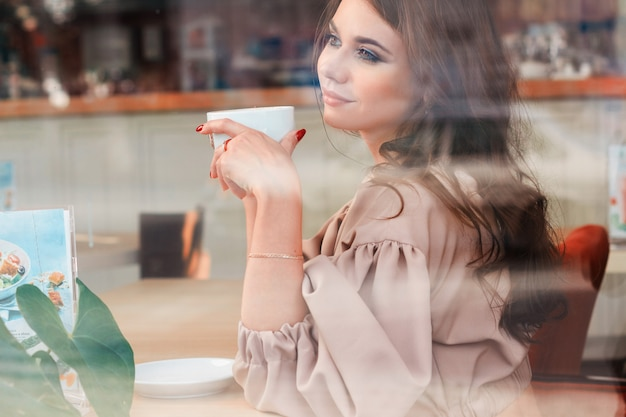 Beautiful girl in dress in cafe and charming smile Premium Photo