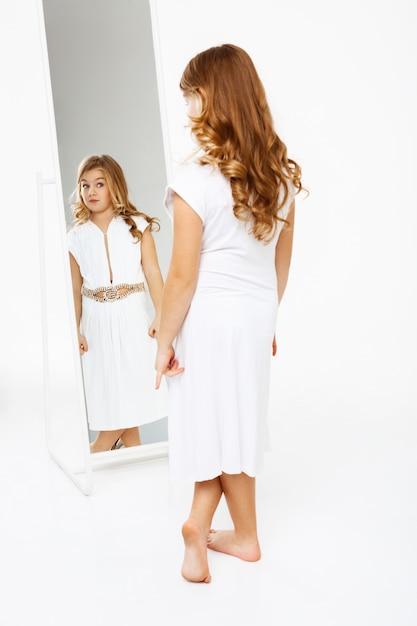 Bella ragazza in abito in piedi davanti allo specchio. Foto Gratuite