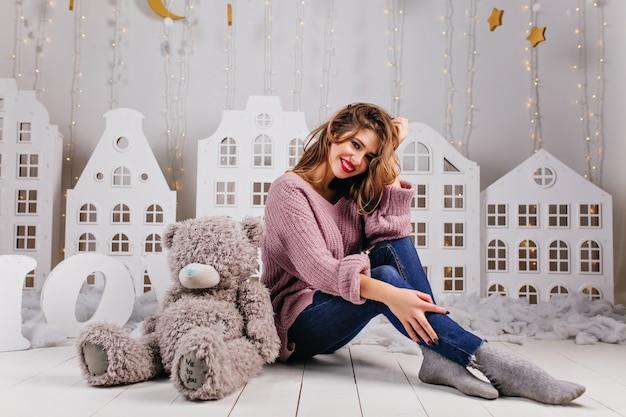 彼女の灰色のテディベアと床に座っている暖かいセーターとジーンズに身を包んだ美しい少女 無料写真