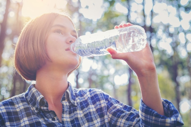 Beautiful girl drinking water from plastic bottle with sunrise Premium Photo