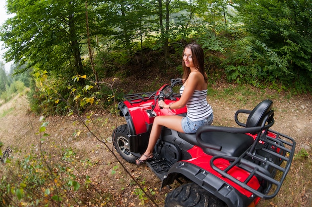 Beautiful girl driving four-wheeler atv Premium Photo