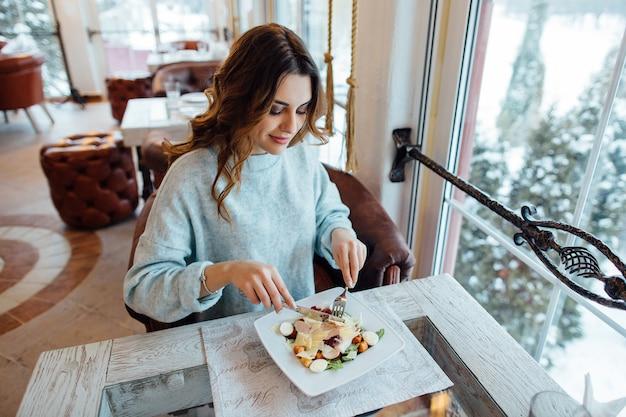 Beautiful girl eating caesar salad in restaurant 8353 6592