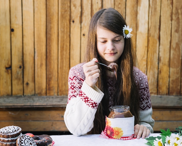 Beautiful girl eating melted chocolate in jar on table Free Photo