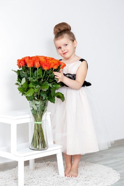 Beautiful girl in elegant dress with a bouquet of orange roses Premium Photo