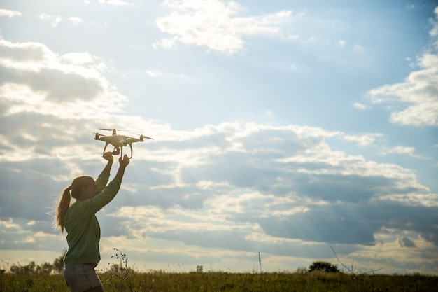 Beautiful girl in a field launches the drone into the sky Free Photo