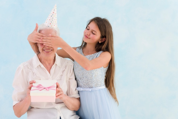 Beautiful girl giving surprised gift by covering her grandmother's eyes Free Photo