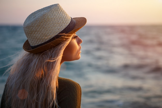 Beautiful girl in hat by the sea at sunset. Premium Photo
