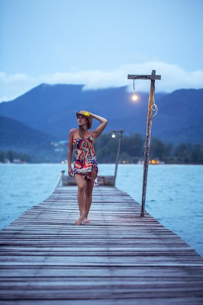 Bella ragazza in cappello sul molo in legno più lungo la sera a koh chang, thailandia Foto Gratuite