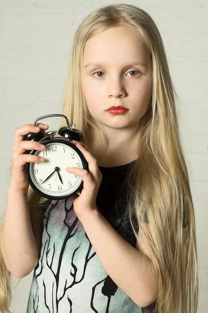 Красивая девушка держит будильник Premium Фотографии