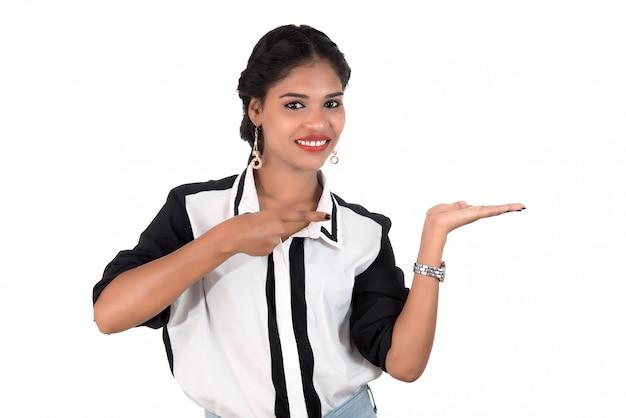 Красивая девушка держит и представляя что-то в руке с счастливой улыбкой. Premium Фотографии