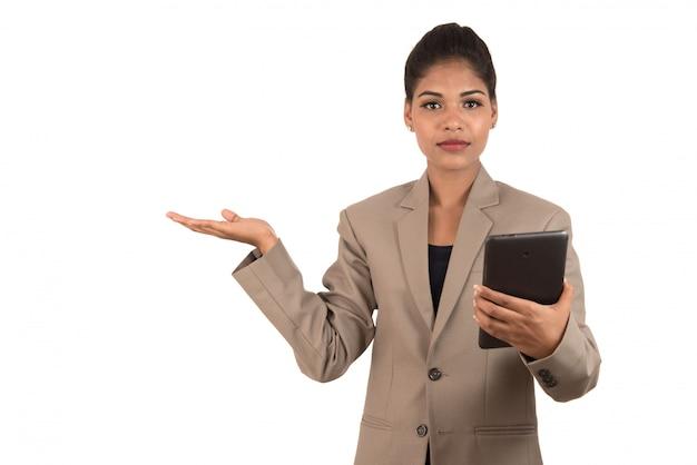 Красивая девушка держит и представляя что-то в руке с смартфона или планшета Premium Фотографии