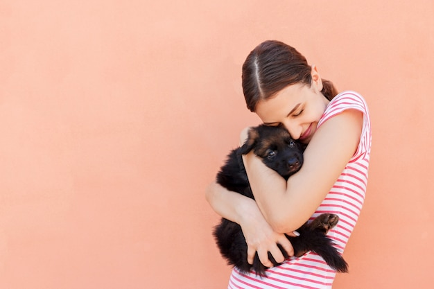 Beautiful girl hugging tight her cute small puppy Premium Photo