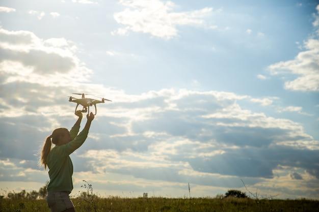 フィールドで美しい少女が空にドローンを起動します 無料写真