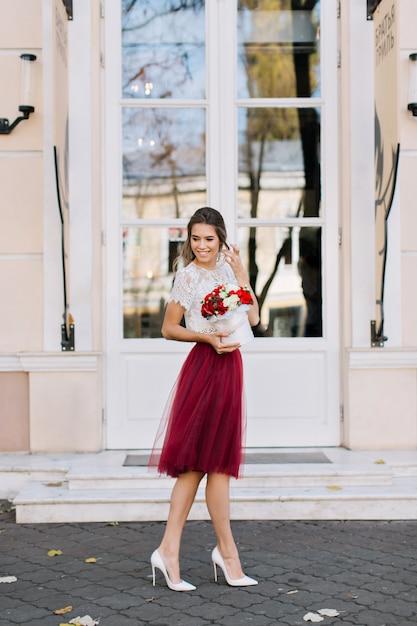 Красивая девушка в юбке из тюля марсала с легкой прической идет по улице. она держит цветы и улыбается в сторону Бесплатные Фотографии