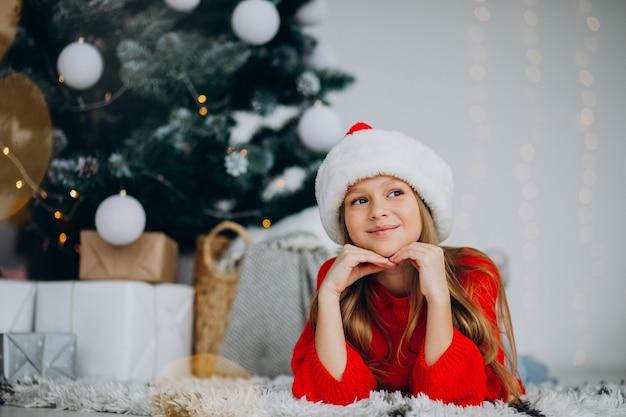 크리스마스 트리 아래 산타 모자에서 아름 다운 소녀 무료 사진