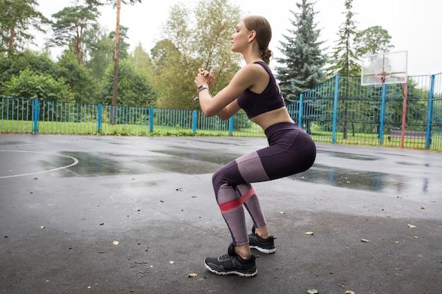 Красивая девушка в спортивном топе и леггинсах тренируется с красной эластичной веревкой на спортивных площадках в парке Premium Фотографии
