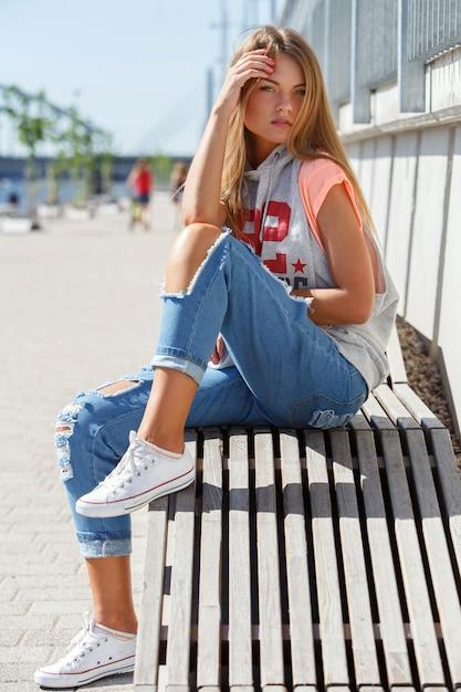 Молодая девка в рваных джинсах