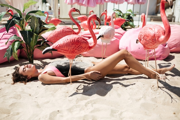 人工ピンクのフラミンゴとビーチの近くに大きな枕と砂の上に横たわっているトレンディな水着の美しい少女。 Premium写真