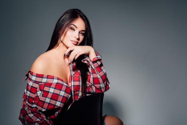 Красивая девушка в футболке с длинными и красивыми волосами на темном фоне. Premium Фотографии