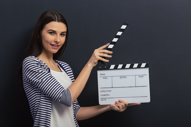 Beautiful girl is holding a clapperboard, looking at camera. Premium Photo