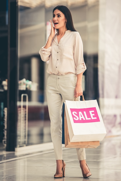 Beautiful girl is holding shopping bags Premium Photo