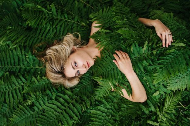A beautiful girl lies in a fern. Premium Photo