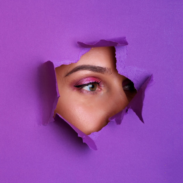 Beautiful girl looks through hole in violet paper background. Premium Photo