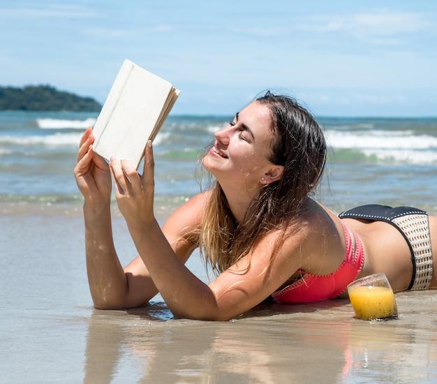新鮮な夏の飲み物とトロピカルフルーツ、休日と本を読んでビーチで横になっている美しい少女 無料写真