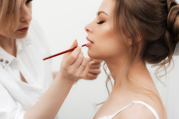 Beautiful Girl Makeup Artist Makes Make Up And Paints Her Lips In A Professional Beauty Salon Premium Photo