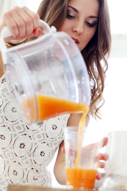 Beautiful girl making orange juice Free Photo