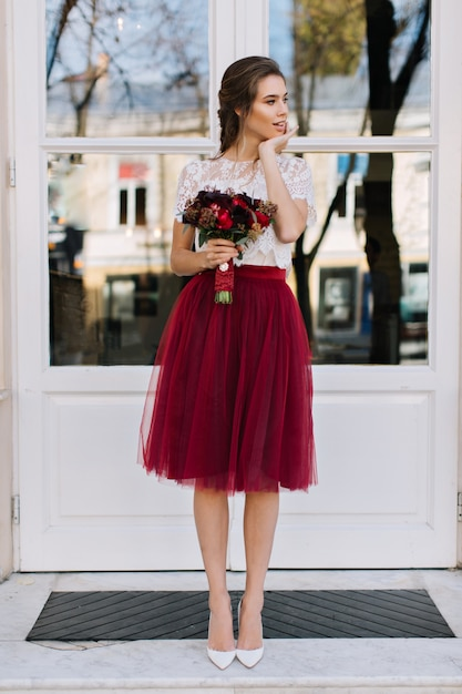 Beautiful girl in marsala tulle skirt on heels walking on street. she holds boquet of  flowers and smiling to side Free Photo