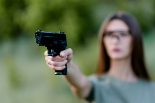Beautiful girl in nature learns to shoot a pistol Premium Photo