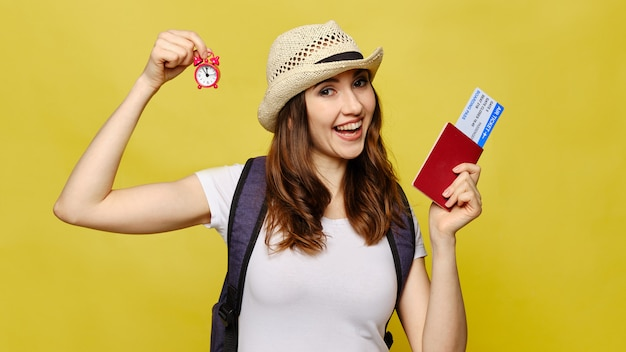 黄色の美しい少女はカメラを見て、パスポートでチケットと時計を保持しています。 Premium写真