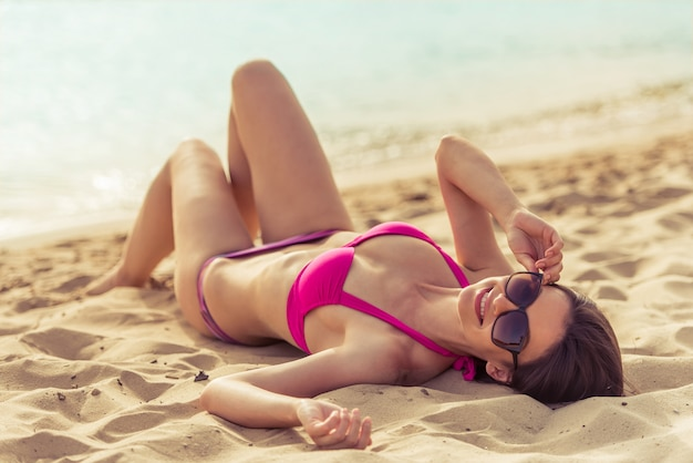 Beautiful girl in pink swimsuit and sun glasses. Premium Photo