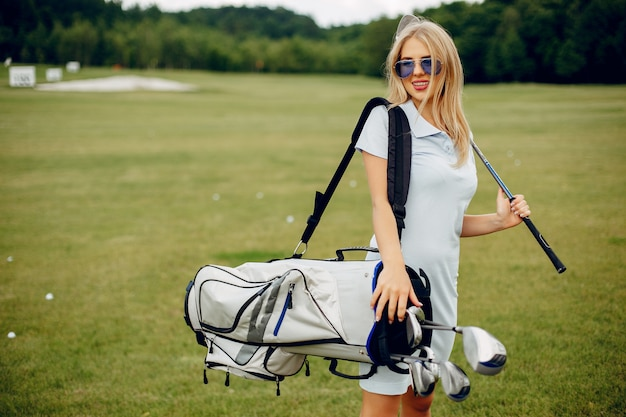 Beautiful girl playing golf on a golf course Free Photo