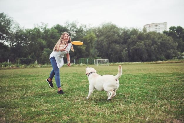 Una bella ragazza che gioca con il suo amato cane nel parco. Foto Gratuite