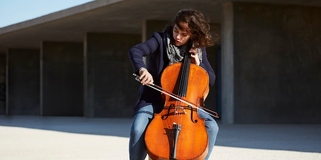 Beautiful girl plays the cello with passion in a concrete environment Free Photo