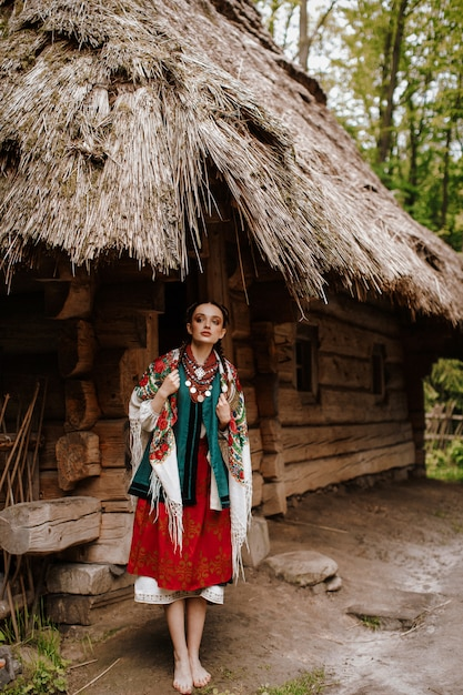 Beautiful girl poses on the courtyards near the house in a traditional ukrainian dress Free Photo