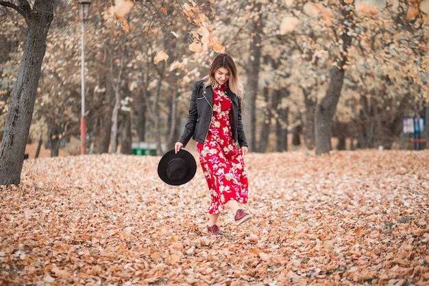 Beautiful girl in a red dress and black jacket walks in the autumn park Premium Photo
