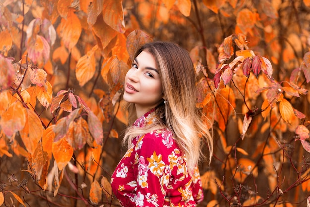 Beautiful girl in a red dress posing in autumn theme Premium Photo