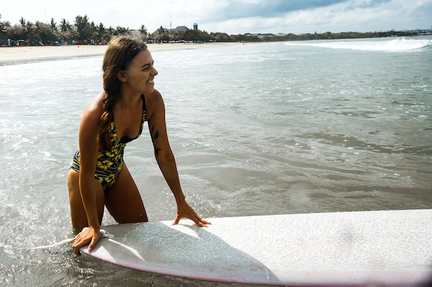 Beautiful girl riding on a surf board on the waves Free Photo