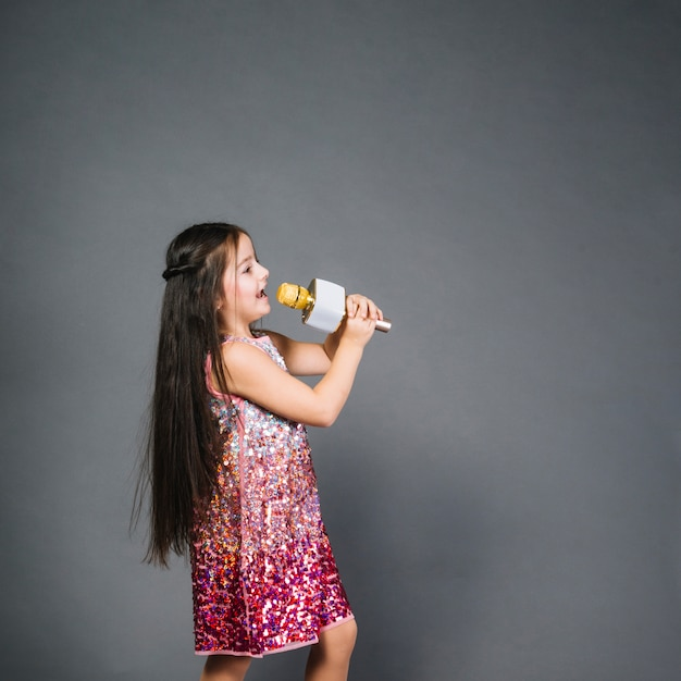 Beautiful girl in sequin dress signing song with microphone Free Photo