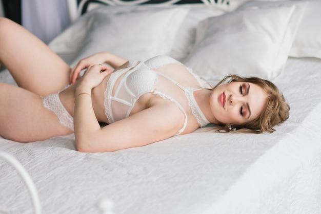 インテリアスタジオの部屋でポーズをとって白い下着の美しい少女セクシーなブルネット Premium写真