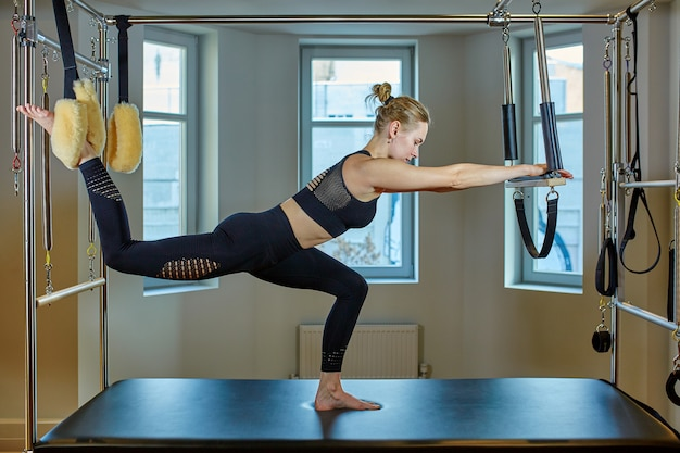 Beautiful girl on the simulator stretches and trains your back, silence gesture Premium Photo
