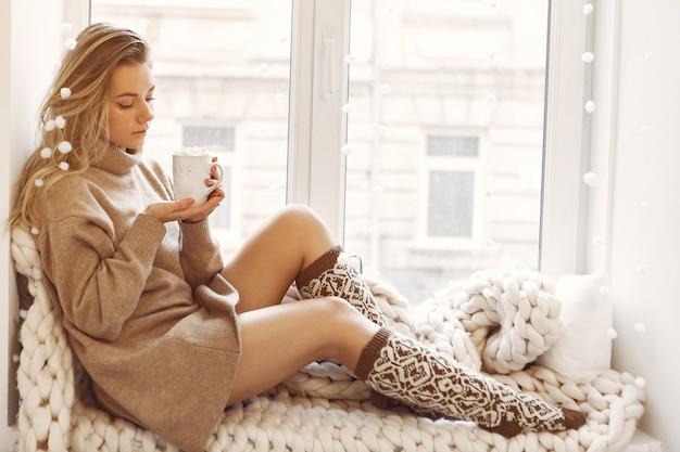 창 근처 집에 앉아 아름 다운 여자 무료 사진