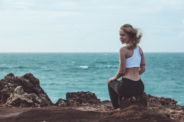 Beautiful girl sitting on a cliff Free Photo