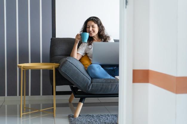 スタイリッシュな部屋のソファにノートパソコンで座っている美しい少女。在宅勤務。機嫌の良い職場環境。 Premium写真